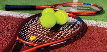 Tennis Rackets and balls on the court.